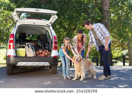 Family getting ready to go on road trip on a sunny day - stock photo