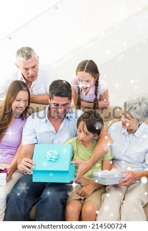 Family gifting birthday present to man against snow falling - stock photo