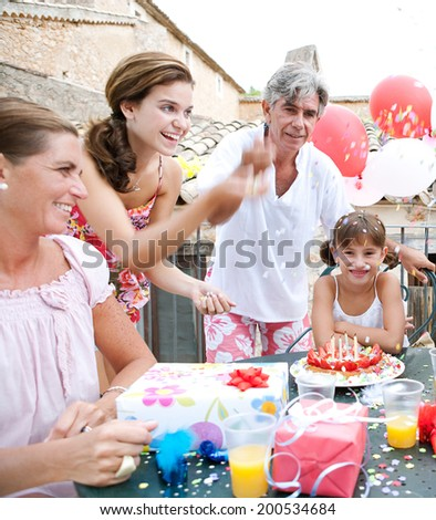 Family group enjoying and celebrating a young girl birthday during a summer day, sitting around a table with a strawberry birthday cake and gifts and throwing confetti. Family celebrating outdoors. - stock photo