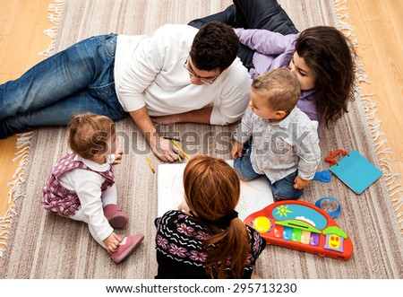 family group of five on the floor - two babies and three adults in the middle of a conversation. - stock photo