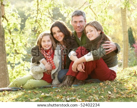 Family Group Relaxing Outdoors In Autumn Landscape - stock photo
