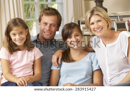 Family Group Sitting On Sofa Indoors