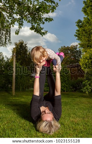 family gymnastics with mother and daughter in the home garden