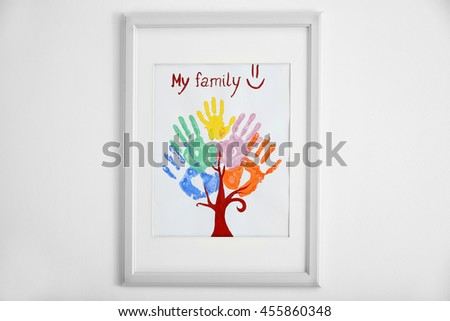 Family hand prints in frame on wall - stock photo