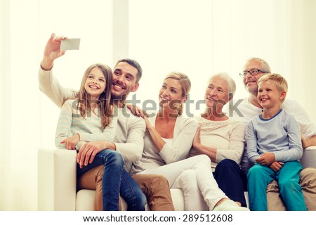 family, happiness, generation and people concept - happy family sitting on couch and making selfie with smartphone at home - stock photo