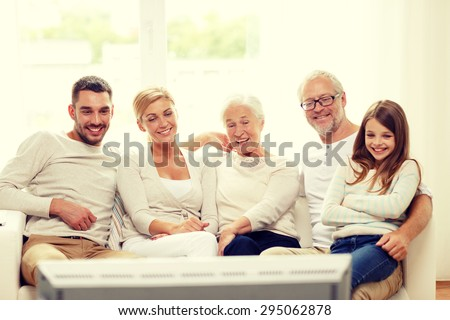 family, happiness, generation and people concept - happy family sitting on sofa and watching tv at home