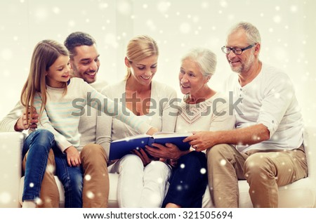 family, happiness, generation and people concept - happy family with book or photo album sitting on couch at home - stock photo