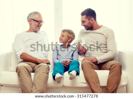 family, happiness, generation and people concept - smiling father, son and grandfather sitting on couch at home - stock photo