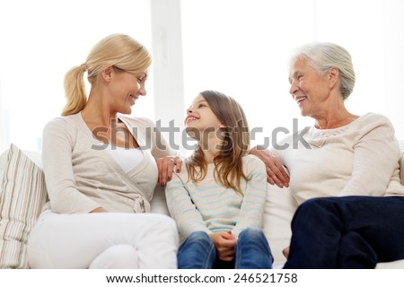 family, happiness, generation and people concept - smiling mother, daughter and grandmother sitting on couch at home - stock photo