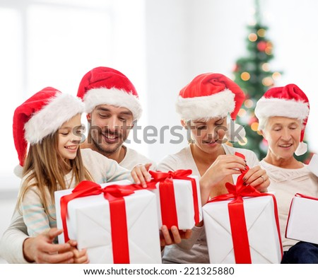 family, happiness, generation, holidays and people concept - happy family in santa helper hats with gift boxes sitting on couch over living room and christmas tree background - stock photo