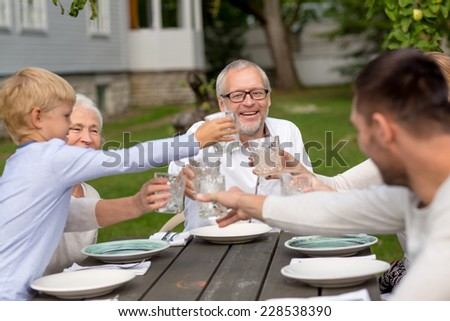 family, happiness, generation, home and people concept - happy family having holiday dinner outdoors - stock photo