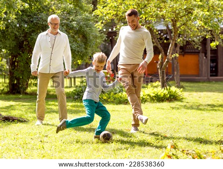 family, happiness, generation, home and people concept - happy family playing football in front of house outdoors - stock photo