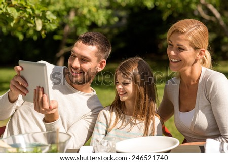 family, happiness, generation, home and people concept - happy family sitting at table and taking selfie with tablet pc computer outdoors - stock photo