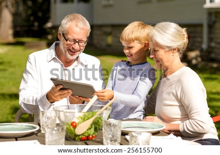 family, happiness, generation, home and people concept - happy family sitting at table with tablet pc computer outdoors - stock photo