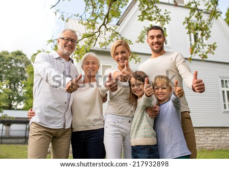 family, happiness, generation, home and people concept - happy family standing in front of house and showing thumbs up outdoors - stock photo