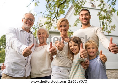 family, happiness, generation, home and people concept - happy family standing in front of house and showing thumbs up outdoors