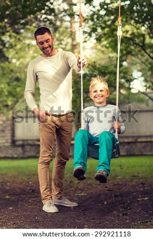 family, happiness, generation, home and people concept - happy father and son swinging on teeterboard outdoors - stock photo