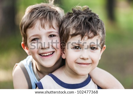 Family happiness - two little smiling child boy brothers walking outdoor - stock photo