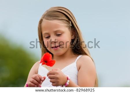 Family - Happy girl with corn poppy in summer - stock photo