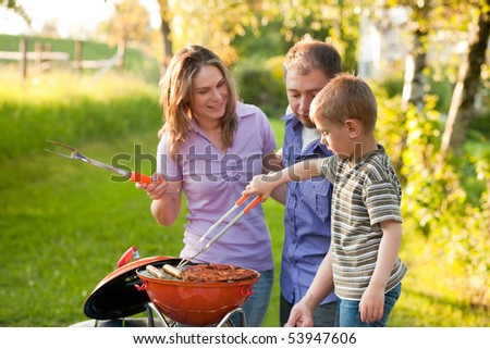 Family having a barbecue party, mother father and son standing around the grill - stock photo