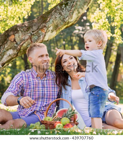 Family having a picnic in the park. Child pointing somewhere.