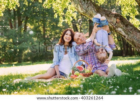 Family having a picnic in the park. Father playing with his son, - stock photo
