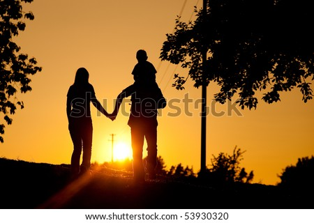 Family having a walk at sunset, the child sitting on his father's shoulders; the whole scene is shot back lit, very tranquil and peaceful - stock photo