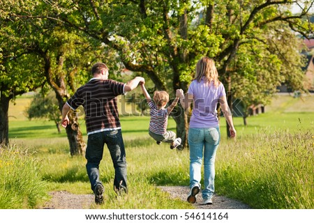 Family having a walk outdoors in summer, throwing their little son in the air in a playful way