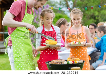 Family having barbecue at garden party, dad is putting corn and grilled vegetables on plates of daughters - stock photo