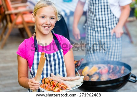Family having barbecue food on grill at family garden BBQ  - stock photo