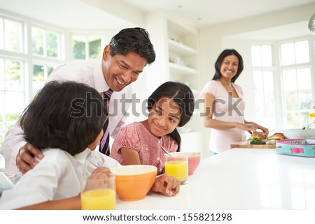 Family Having Breakfast Before Father Leaves For Work - stock photo