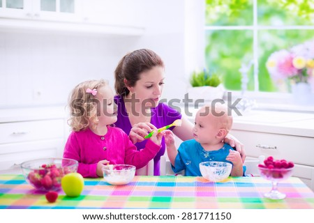 Family having breakfast in a white sunny kitchen. Young mother feeding two kids, eating fruit and dairy. Healthy nutrition for children. Parent with toddler kid and baby cooking morning meal. - stock photo