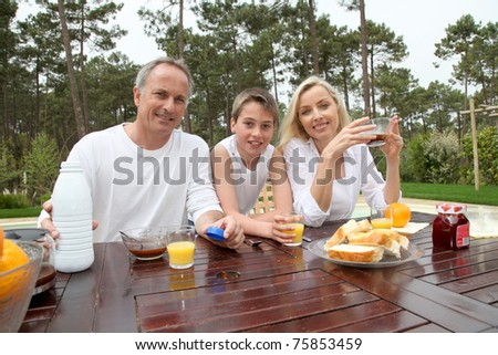 Family having breakfast in house garden
