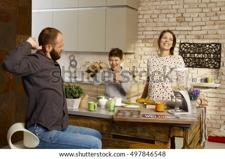 Family having breakfast in the kitchen, parents stretching, little boy laughing.