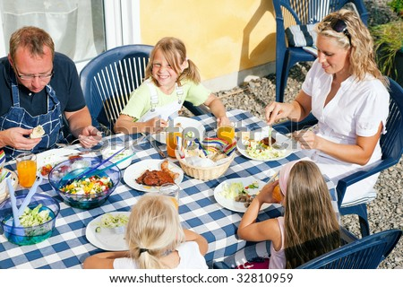 Family having dinner in their garden - barbecue stuff and salad - stock photo