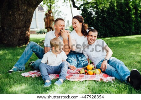 family having fun at a picnic. parents and two sons