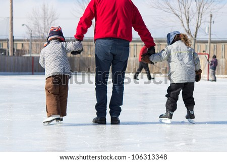 Family having fun at the outdoor skating rink in winter. - stock photo