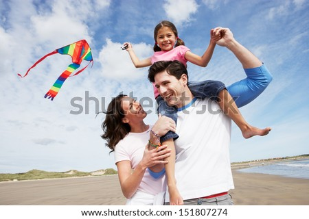 Family Having Fun Flying Kite On Beach Holiday - stock photo