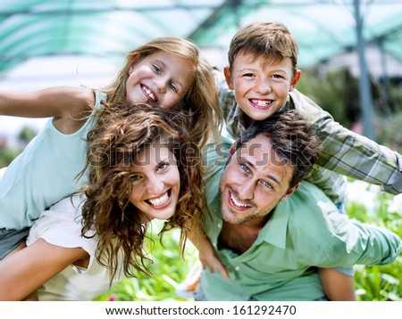 family having fun in a greenhouse - stock photo