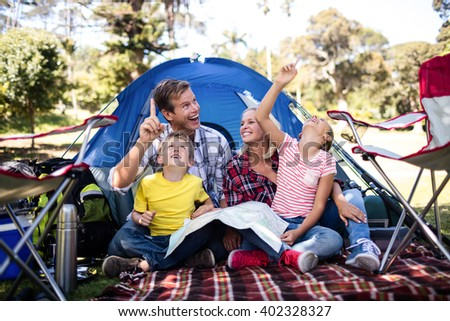 Family having fun in front of a tent in park