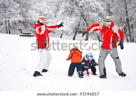 Family having fun in snow - stock photo
