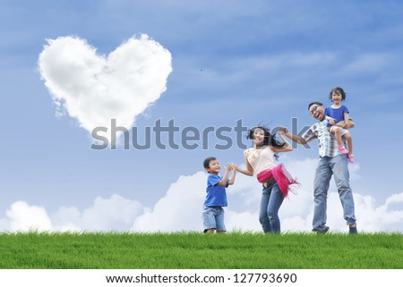 Family having fun in the park under heart shape clouds - stock photo