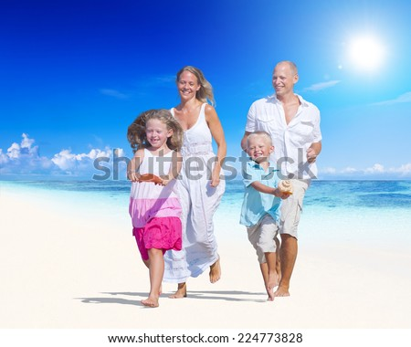 Family having fun on a beach. Young family enjoying their summer vacation. - stock photo