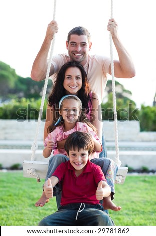 Family having fun on a swing - stock photo