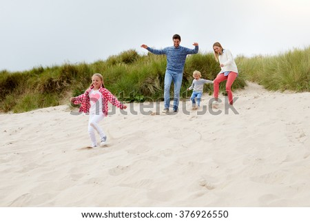 Family Having Fun On Beach Together - stock photo