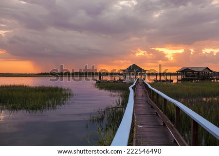 family having fun on dock at sunset with approaching storm - stock photo