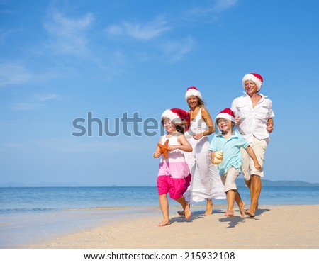 Family having fun on the beach on Christmas. - stock photo