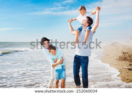 family having fun on the beach to the sea - stock photo