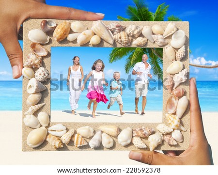 Family having fun on the beach with picture frame. - stock photo