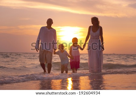 Family having fun on vacation with perfect sunset. - stock photo